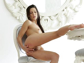 Brunette poses invitingly before masturbating